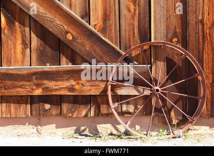 Old Wild West Wagon Wheel – Old western metal rusty wagon wheel leaning up against an old wooden brown barn door - Stock Photo