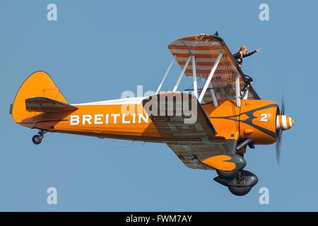 Breitling Wing Walkers in their distinctive orange Boeing Stearman vintage biplanes. - Stock Photo