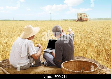 Two farmers sitting in field talking - Stock Photo