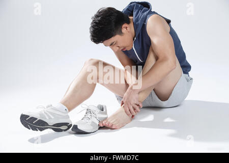 Man feeling pain in the ankle - Stock Photo