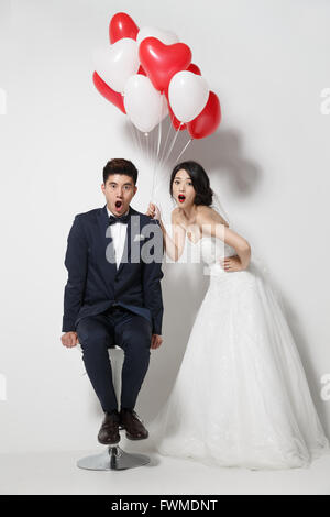Bride and groom with bouquet and heart-shaped balloons