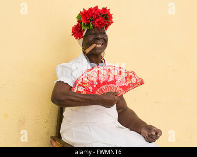 Horizontal portrait of a lady posing with a large Cohiba cigar in Cuba. - Stock Photo