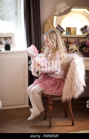 girl playing with her baby doll. day care, kid, playroom, pretend game. - Stock Photo