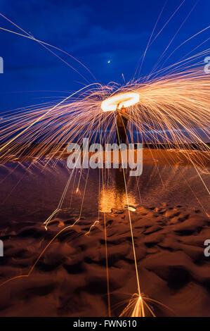 Wire wool spinning on Hayling Island beach - Stock Photo