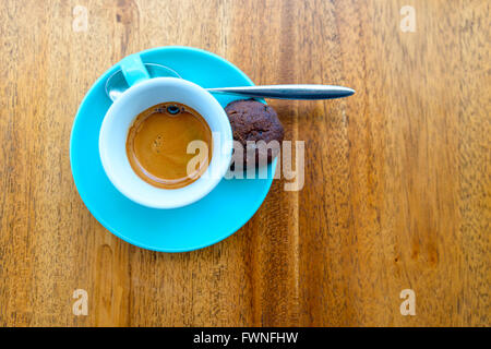 An espresso in a turquoise cup on a wood table - Stock Photo