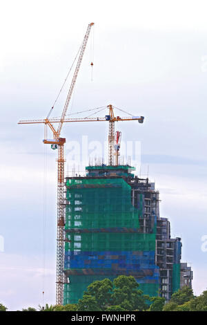 Skyscraper Office Tower Under Construction with two Cranes in Pattaya Thailand - Stock Photo