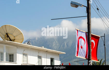 Satellite dish on a rooftop in front of an unfinished building in the city of Kyrenia, North Cyprus. - Stock Photo