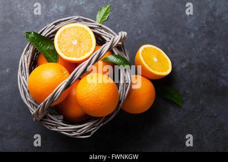 Fresh ripe oranges in basket on dark stone background. Top view - Stock Photo