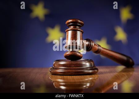 Mahogany wooden gavel on glossy wooden table. Flag of European Union, EU,  in the background. - Stock Photo