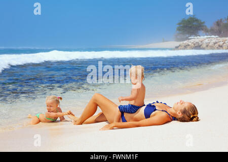 Happy family - mother, baby son and daughter lying on sand beach and look at sea surf after swimming in clear water. - Stock Photo