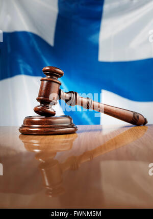 Mahogany wooden gavel on glossy wooden table, flag of Finland in the background. - Stock Photo