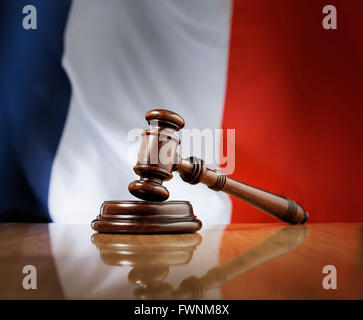 Mahogany wooden gavel on glossy wooden table, flag of France in the background. - Stock Photo