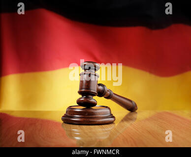 Mahogany wooden gavel on glossy wooden table, flag of Germany in the background. - Stock Photo