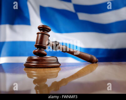 Mahogany wooden gavel on glossy wooden table, flag of Greece in the background. - Stock Photo