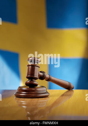 Mahogany wooden gavel on glossy wooden table, flag of Sweden in the background. - Stock Photo