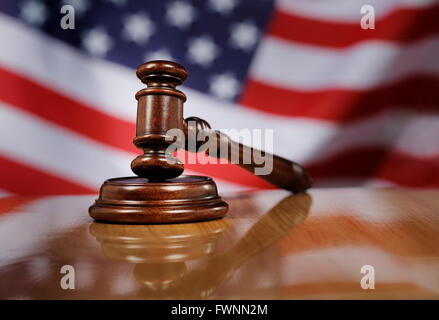 Mahogany wooden gavel on glossy wooden table, USA flag in the background. - Stock Photo