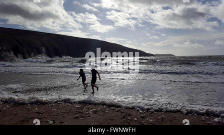 Mwnt Beach, Cardiganshire, West Wales, UK. 6th April, 2016. Weather Children play in the sea during the Easter Holidays - Stock Photo