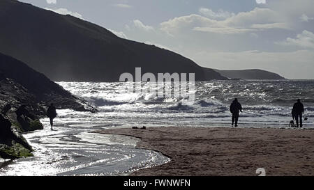 Mwnt Beach, Cardiganshire, West Wales, UK. 6th April, 2016. Weather Holiday makers watch the waves during the Easter - Stock Photo