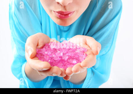 Well groomed female hands they keep pink, pastel crystals. - Stock Photo