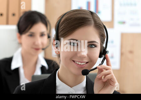 Portrait of call center worker accompanied by her team. Smiling customer support operator at work. Help and support - Stock Photo