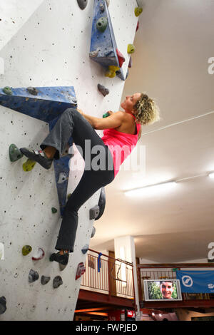 Young teen girl climbs up an artificial climbing wall ...