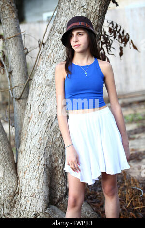 Young twelve year old preteen girl under a tree (model release available) - Stock Photo