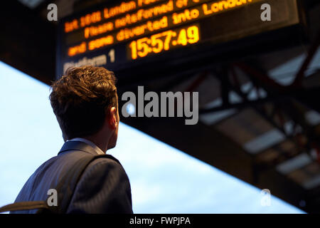 Businessman Stands On Platform Waiting For Train To Arrive - Stock Photo