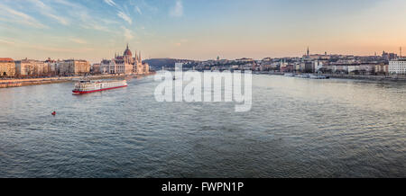 Tour boat sails down the River  Danube outside the Hungarian parliament building in Budapest, Hungary. - Stock Photo