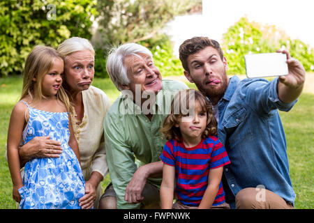 Happy father taking selfie with family in yard - Stock Photo
