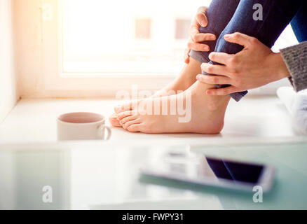Feet of unrecognizable woman sitting on window sill - Stock Photo