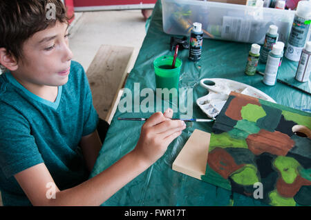 boy at camp painting a birdhouse craft project - Stock Photo