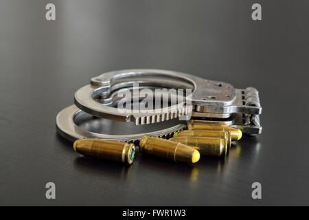 Police handcuffs and pistol bullets on dark table closeup - Stock Photo