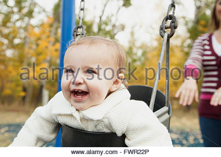 Mother pushing baby girl on swing in park - Stock Photo