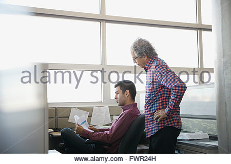 Businessmen analyzing documents in office cubicle - Stock Photo
