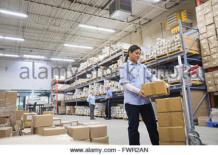 Female worker stacking boxes in warehouse - Stock Photo
