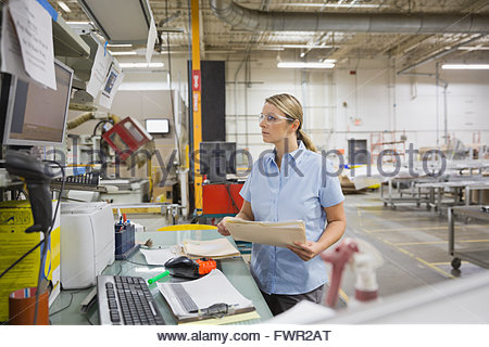 Worker with documents using computer in factory - Stock Photo