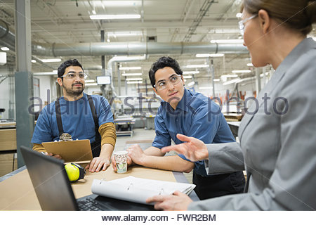 Manager and manual workers talking in factory - Stock Photo