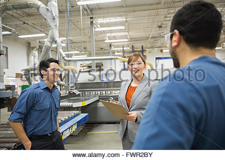 Manager and workers meeting in factory - Stock Photo