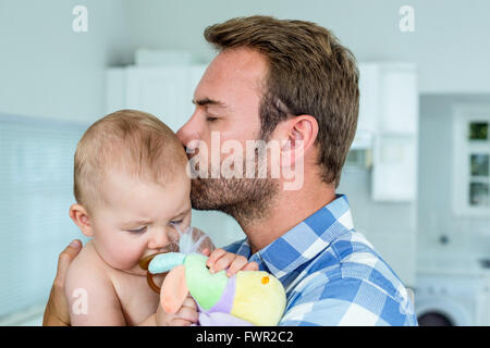 Father kissing playful son in kitchen at home - Stock Photo