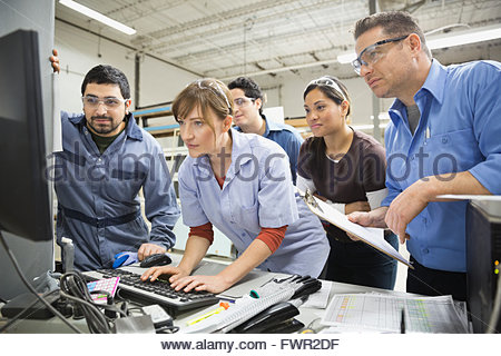 Workers using computer in warehouse - Stock Photo