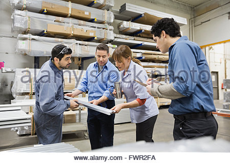 Workers examining metal parts in warehouse - Stock Photo