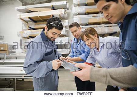Workers examining metal in warehouse - Stock Photo