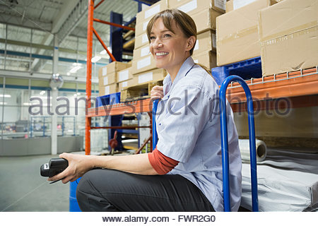 Female working smiling in warehouse - Stock Photo