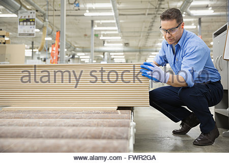 Worker examining wooden planks in factory - Stock Photo