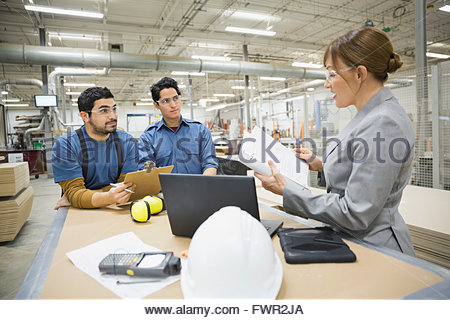 Manager discussing with workers in factory - Stock Photo