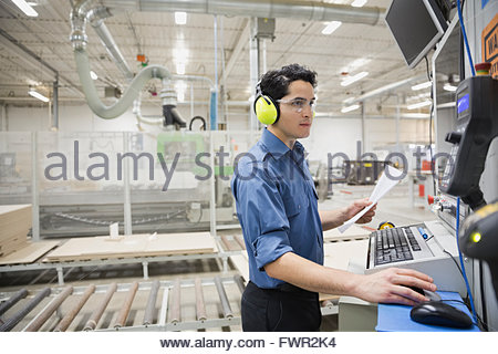 Worker using computer in factory - Stock Photo