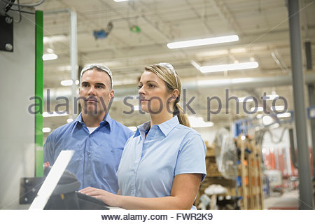 Workers using computer in manufacturing warehouse - Stock Photo
