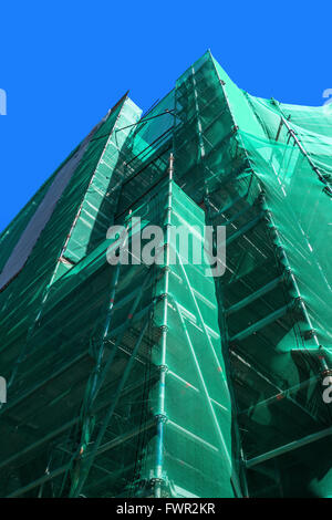 Scaffolding with green safety net - Stock Photo