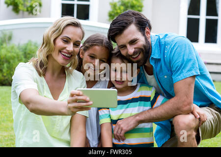 Mother taking selfie with family in yard - Stock Photo
