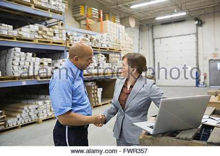 Manager and worker shaking hands in warehouse - Stock Photo